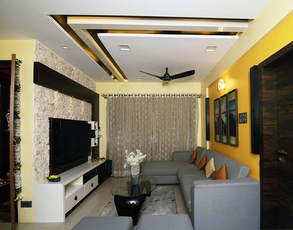 living room having tv unit grey color Sofa yellow sofa with pop false ceiling